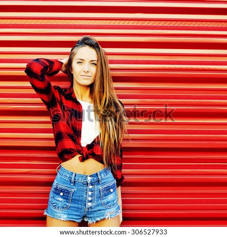 Attractive young woman posing near a red wall - copyspace  - stock photo