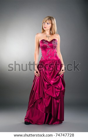 attractive young woman posing on studio neutral background wearing purple gown - stock photo