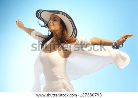 Attractive young woman pretending to fly, enjoying sun and wind eyes closed. - stock photo