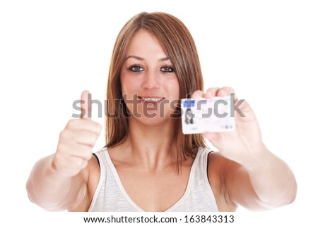 Attractive young woman proudly showing her drivers licence. Details on drivers licence have been changed and blurred out. All on white background. - stock photo
