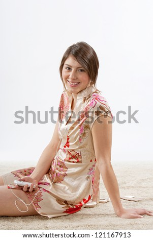 Attractive young woman relaxing and sitting on the carpet at home while listening to music with her earphones, smiling. - stock photo