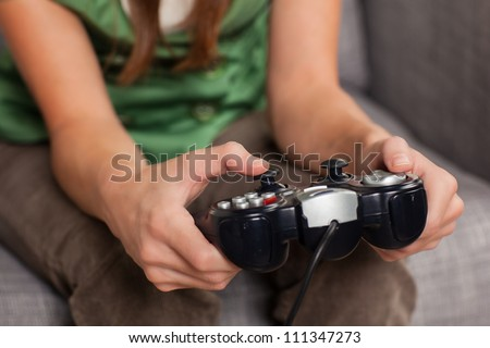 Attractive young woman relaxing at home playing a game holding controller sitting on couch. - stock photo