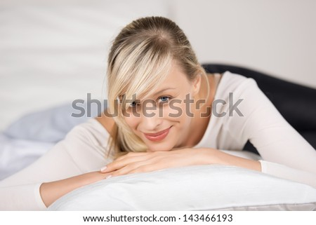 Attractive young woman relaxing in her bedroom - stock photo