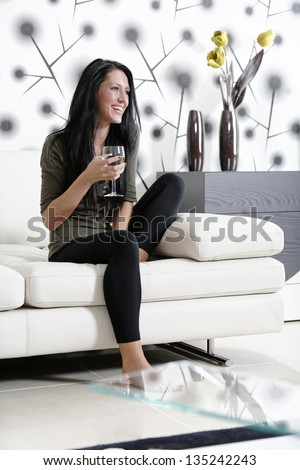 Attractive young woman relaxing on her sofa at home with a glass of white wine. - stock photo