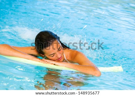 Attractive young woman relaxing under cascade in spa pool. - stock photo
