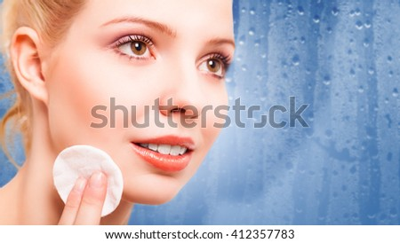 attractive young woman removing makeup - stock photo