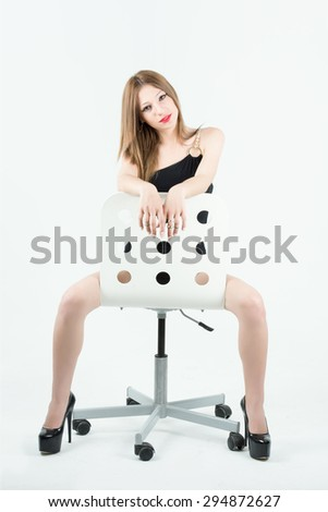Attractive young woman reverse sitting on chair with black dress and high heels - stock photo