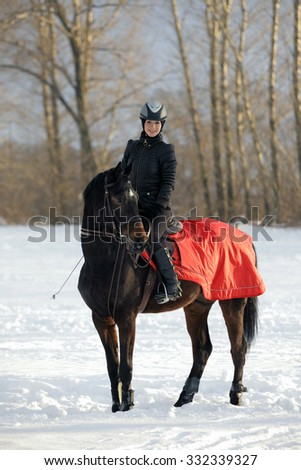 Attractive young woman riding a horse in the snow  - stock photo