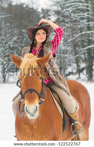 Attractive Young Woman Riding a Horse the Snow - stock photo