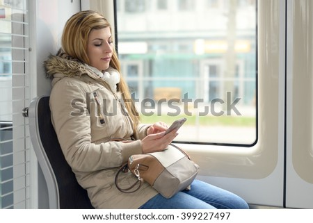 Attractive young woman riding as a passenger in a train sitting alongside a window reading messages on her mobile phone with a smile, profile view - stock photo