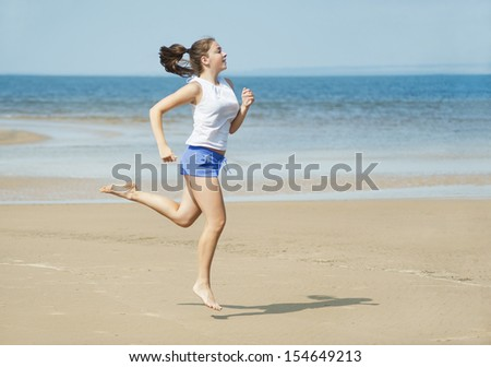 Attractive young woman running alone on the beach - stock photo