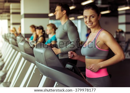 Attractive young woman running on a treadmill in gym, looking at camera and smiling - stock photo