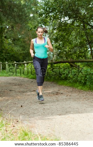 attractive young woman running through a forest - stock photo