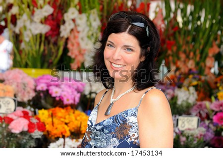 Attractive Young Woman Shopping For Flowers At The Farmers Market - stock photo