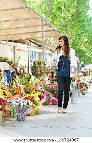 Attractive young woman shopping in an outdoors fresh flowers market, walking and carrying paper bags while looking at the colorful selection of the floral bouquets during a sunny day. - stock photo