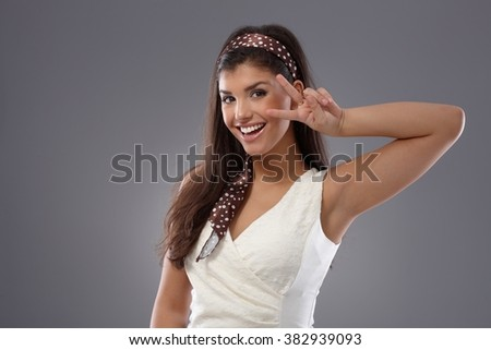 Attractive young woman showing victory sign, smiling happy. - stock photo