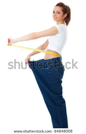 Attractive young woman shows her old huge jeans, successful dieting concept, isolated on white - stock photo