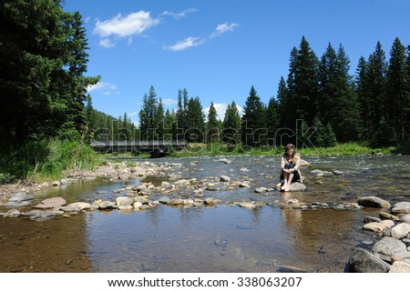 Attractive young woman sits on a rock in the middle of the Gallatin River in Montana.  She is smiling and barefoot with jeans rolled up. - stock photo