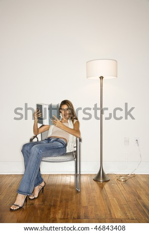 Attractive young woman sitting back in a silver chair and reading a book next to a floor lamp. Vertical shot. - stock photo