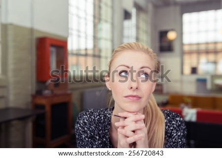Attractive young woman sitting daydreaming in a large studio apartment looking up into the air with a faraway serious expression and her chin on her hands - stock photo