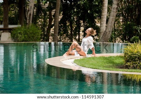 Attractive young woman sitting down at the edge of a swimming pool, relaxing in a tropical garden. - stock photo