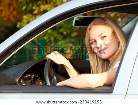 Attractive young woman sitting in her car. - stock photo