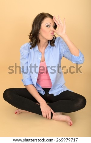 Attractive Young Woman Sitting on the Floor Wearing a Blue Shirt and Black Leggings Pulling Silly Facial Expressions and Acting the Fool - stock photo