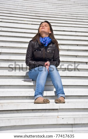 Attractive young woman sitting on the marble steps and tans. Sunlight. Eyes closed. - stock photo