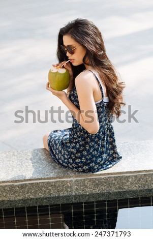 Attractive young woman sitting on the parapet and drinking coconut milk - stock photo
