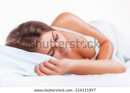 Attractive young woman sleeping in bed on a light background - stock photo
