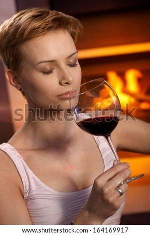 Attractive young woman smelling glass of wine, enjoying drink by fireplace. - stock photo