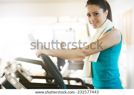 Attractive young woman smiling and doing cardio exercise on treadmill at gym. - stock photo