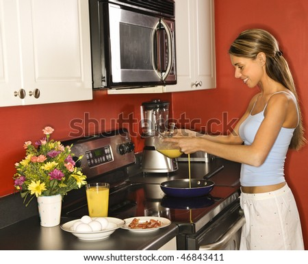 Attractive young woman smiling in her kitchen while cooking breakfast. She is dressed in sleepwear. Horizontal shot. - stock photo