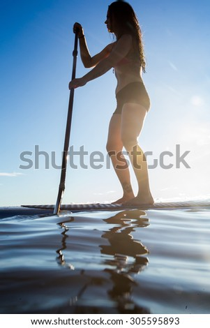 Attractive Young Woman Stand Up Paddle Boarding, Active Beach Lifestyle - stock photo