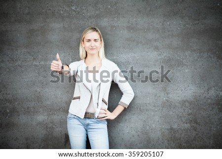 Attractive young woman standing in front of concrete wall - stock photo