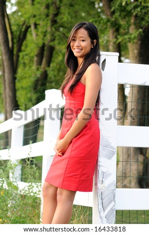Attractive young woman standing in front of white fence - stock photo