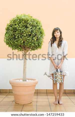 Attractive young woman standing proudly next to her topiary tree plant on a roof terrace holding a full watering can while doing her gardening, smiling. - stock photo