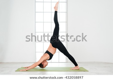 Attractive young woman stretching and practicing yoga - stock photo