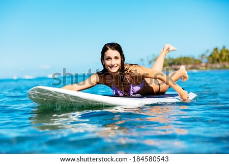 Attractive Young Woman Surfing in Hawaii, Paddling out to the Lineup - stock photo