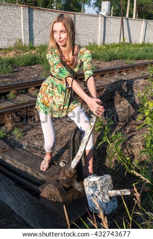 Attractive young woman throws old style railway switch - stock photo