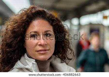 Attractive young woman travelling on a train looking at the camera with a quiet smile, close up head shot - stock photo