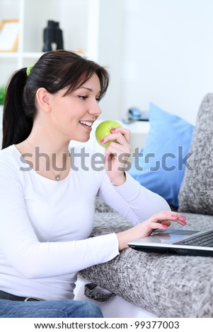 Attractive young woman using laptop and eating apple - stock photo