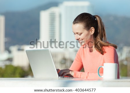 Attractive young woman using laptop outdoors.   - stock photo