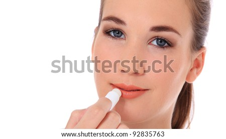 Attractive young woman using lip balm. All on white background. - stock photo