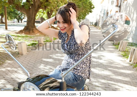 Attractive young woman using the mirrors on her motorbike to do her hair up on a sunny day, outdoors. - stock photo