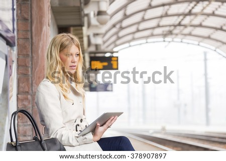 Attractive young woman waiting for a train at the station sitting on a bench on the platform with her tablet computer in her hand - stock photo