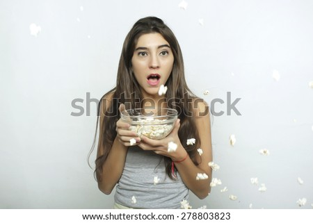Attractive young woman watching a movie with popcorn - stock photo