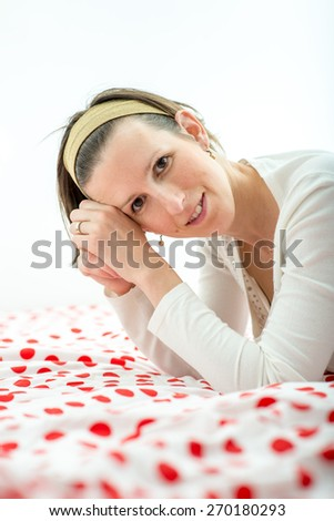 Attractive young woman wearing an headband in her hair leaning on her elbows on a colourful duvet with red polka dots smiling at the camera. - stock photo
