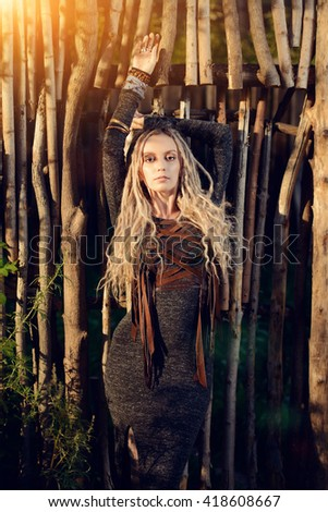 Attractive young woman wearing clothes in boho style posing by a wooden fence. - stock photo