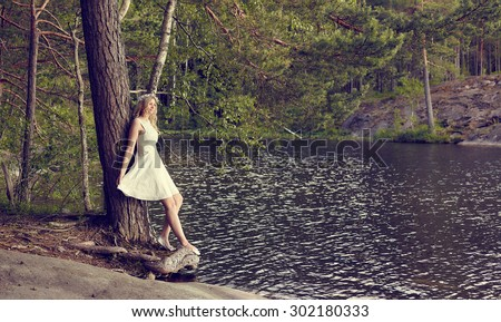 Attractive young woman wearing white summer dress and she leans towards the pine, sunny summer day, lake on background - cross processed image - stock photo